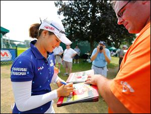 Defending champion So Yeon Ryu signs an autograph for Mike Dee of Madison Heights, Mich.