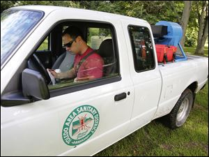 Myles Caryer of Toledo Area Sanitary District Mosquito Control checks his next stop after spraying for mosquitoes on Wolfinger Road.
