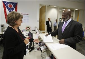 Incumbent Mayor Mike Bell hands petitions to Lori Jacek as files to run for reelection at the Lucas County Board of Elections in Toledo last week.