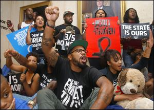 Protesters staged a sit-in outside Florida Gov. Rick Scott's office on Tuesday  in response to the not guilty verdict in the trial of George Zimmerman, the Florida neighborhood watch volunteer who fatally shot Trayvon Martin.