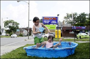 Kristianna Reno, 4, left, and Riley Funk, 6, try to cool off at East Broadway and Mason Street in East Toledo. Humidity is helping high temperatures feel hotter.