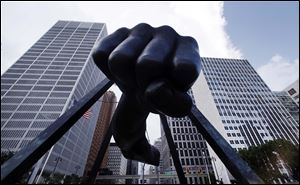 The Detroit skyline rises behind the Monument to Joe Louis, also known as