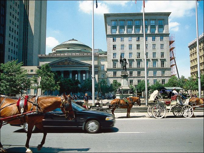 Carriages and tourists gather at Place d'Ames, which is the gateway to Old Montreal and the front yard for the Pantheon-inspired Bank of Montreal. The Canadian city, where residents speak both French and English, is rich in history.