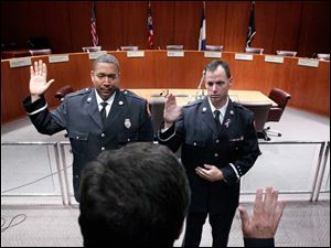 Toledo Fire and Rescue Department Battalion Chief Dave Dauer, center, swears in Toledo Fire and Rescue members Verdell Franklin, left, and  Joseph Camerato, right, to be promoted to Captains.