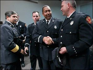 Toledo Fire Chief Luis Santiago, left,  stands nearby while Verdell Franklin, left, and Jon-Paul Thibert, right, congratulate each other for being promoted Wednesday.