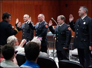 Toledo Fire and Rescue Department Battalion Chief Dave Dauer, far left, swears in Toledo Fire and Rescue members from left: Randy Coy, Daniel O'Leary, Jim Schulty, and  Jon-Paul Thibert, to become Lieutenants.