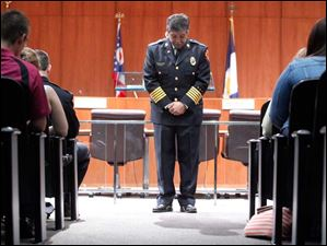 Toledo Fire Chief Luis Santiago takes a moment of silence to honor fallen firefighters during a ceremony to promote members of the Toledo Fire Department in Toledo City Council Chambers Wednesday.