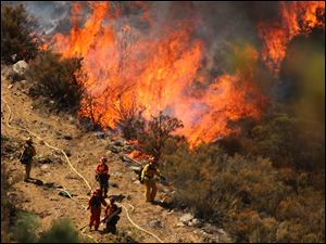 A female inmate hand crew from Puerta La Cruz and firefighters in an engine company with them set fire to reinforce the line to stave off part of the Mountain Fire burning up a hill toward them on Tuesday near Lake Hemet, Calif.