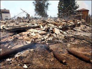 What remains of a home destroyed by the Mountain Fire smolders Tuesday in Pine Springs Ranch, Calif.