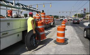 Construction workers remove orange barrels from the Secor Road-Central Avenue intersection that reopened on Friday.