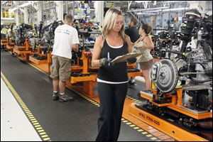 Chrysler Group employees work on the new Cherokee line at the Jeep Assembly complex in Toledo. Production of the new model began June 24, and workers eventually will be able to produce 896 vehicles a day.