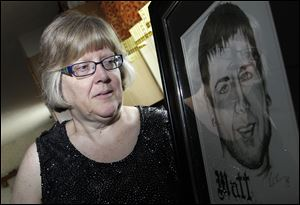 Jerri Jackson, mother of Aurora, Colo. theater shooting victim Matthew McQuinn, stands next to a sketch of her son in Springfield, Ohio.