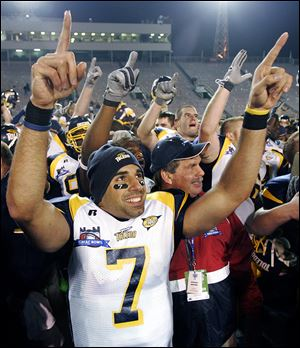 Bruce Gradkowski celebrates the Rockets' win in the GMAC Bowl in 2005. His restaurant includes many photos of UT sports.