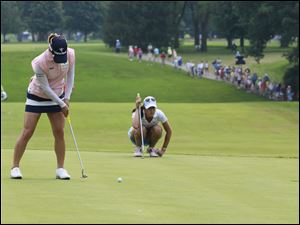 Defending champion Se Yeon Ryu, left, putting while Michelle Wie lines up her shot.