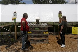 Kim McCance, of Weston, right, and a man who declined to be named, left, read up on the insect hotel outside the Horticulture Barn.