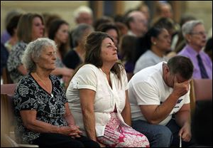 The grandmother, left, mother, and father of Aurora movie theater shooting victim Micayla Medek mourn during a memorial mass held for families and supporters of those killed, at St. Michael the Archangel Catholic Church, in Aurora, Colo.