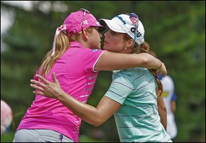 Paula Creamer, left, hugs Beatriz Recari after they finished the 18th hole. Creamer and Recari are tied for the lead going into today.