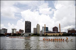 Teams face off during a race at the 12th annual Grand Maumee Dragon Boat Festival on the Maumee River. The festival on Saturday featured races of teams in 40-foot-long boats with up to 20 rowers. The Hong Kong-style boats are based on ancient Chinese designs, complete with head and tail. The festival, which had free admission, also included crafts, origami, calligraphy, and Chinese kite-flying. Proceeds from the event benefit Partners In Education.
