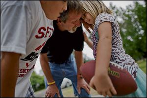 David Schooley, 57, center, huddles with his children, Nathaniel, 12, and Hannah, 6, while playing football in his front yard.