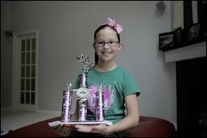 Laci MacQuisten, 9,  of Temper-ance took home a large trophy from the Michigan pageant and qualified for the national pageant in Anaheim, Calif., in November.