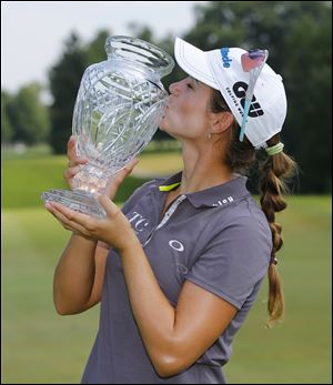 Beatriz Recari kisses the trophy after winning the Marathon Classic today at Highland Meadows Golf Club in Sylvania.