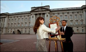 At Buckingham Palace, Ailsa Anderson, the queen's press secretary, with Badar Azim, a footman, places the official announcement of the birth of the third-in-line to the throne.