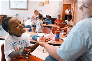 Charlie Sarver, 6,  laughs as his teacher, Erika Henson cleans paint off his hands after working on an art project in the Prescribed Pediatric Center, a section devoted to children with disabilities.