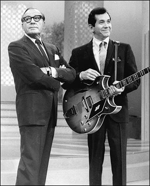 Comedian Jack Benny was known as a master of comic timing.  This was the expression that accompanied his famous 'Hmm-m-m.' Here he's inflicting it on singer-guitarist Trini Lopez in November, 1966.