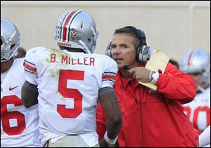Ohio State head coach Urban Meyer talks with quarterback Braxton Miller (5) during the fourth quarter of an NCAA college football game against Michigan State at Spartan Stadium in East Lansing, Mich., Saturday, Sept. 29, 2012.  Ohio State held off No. 20 Michigan State 17-16 giving Urban Meyer a win in his first Big Ten game as Buckeyes coach. (AP Photo/Carlos Osorio)