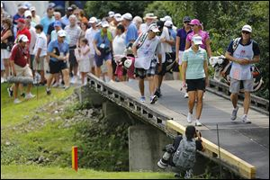 The group of Beatriz Recari, Paula Creamer, and Alison Walshe cross the bridge on the 18th hole.