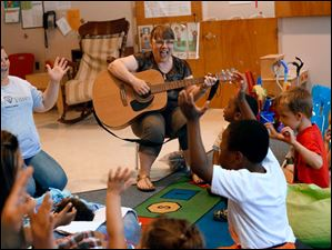 Donise Woodard, an early intervention specialist with the Lucas County Board of Developmental Disabilities, center, laughs as she leads a classroom of children in song at the Prescribed Pediatric Center at the EduCare Center.