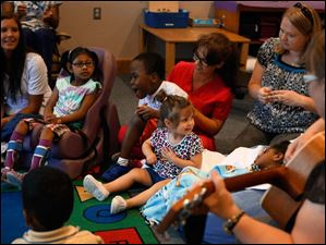 Kendall Hattery, 2, center, turns to look at her teacher while participating with her classmates in a sing along during class at the Prescribed Pediatric Center.