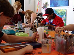 Marc Arnett, center, and other artists work on their individual pieces at the Shared Lives Studio.