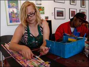 Shanna Richie, left, works on creating a weaving with pieces of canvas and Plexiglass glass as Marc Arnett works on a skyline of New York City during an art session at the Shared Lives Studio.
