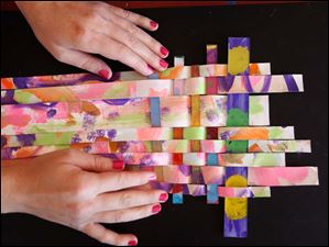 Shanna Richie weaves pieces of painted canvas and Plexiglass together during an art session.