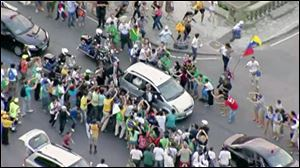 In this image from video, a crowd mobs the silver Fiat carrying Pope Francis through Rio de Janeiro on Monday, July 22, 2013. Ecstatic believers forced the closed Fiat to stop several times as they swarmed around during the drive from the airport to an official opening ceremony in the center of the city.