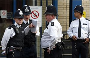 British police officers discuss outside St. Mary's Hospital exclusive Lindo Wing.