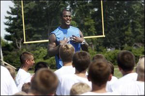 Detroit Lions' linebacker Tahir Whitehead jokes with football camp participants during a break in drills at Sylvania Northview on Tuesday. The four-day camp ends Thursday.