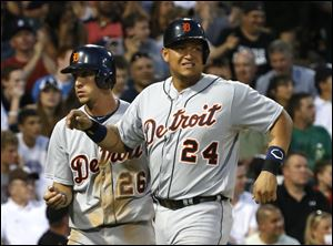 Detroit Tigers' Miguel Cabrera, right, grimaces after scoring with Hernan Perez, left, on a single by Victor Martinez, off a pitch by Chicago White Sox starting pitcher Chris Sale.