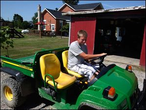 Trevin gets behind the wheel of his utility vehicle, which he uses to tend his acre a mile from his home.