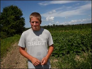 Trevin Haar, 17, smiles as he stands before a large portion of his one-acre garden in Woodville. Haar first began gardening a small plot when he was 10 years old.