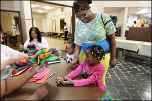 Ashley Fowlkes, center, helps her children Krystal Morris, 3, left, and Myanna Morris, 4, right, with crafts after registering them for Head Start at the J.B. Simmons Community Center in May.
