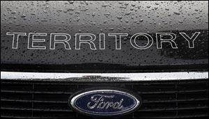 In this Thursday, May 23, 2013, photo, rain falls on a car at a Ford dealership in Sydney, Australia. Ford Motor Co. reports quarterly earnings on Wednesday, July 24, 2013. (AP Photo/Rick Rycroft)