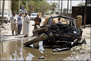 Civilians inspect the aftermath of a car bomb attack in Baghdad, Iraq, Wednesday, July 24, 2013. A bomb exploded near a Sunni mosque in Baghdad's southern Dora neighborhood on Tuesday, killing several people and wounding many more,  police said.
