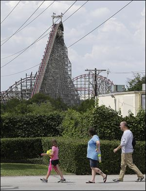 The Texas Giant roller coaster ride sits idle as people walk outside the Six Flags Over Texas park Saturday in Arlington. Investigators will try to determine if a woman who fell to her death from the roller coaster was properly secured by ride operators.