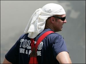 Toledo firefighters Paul Heiss keeps cool while battling a fire at the Tate Funeral home, 1003 Broadway, Toledo, Ohio, Sunday, July 11, 2010.