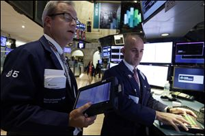 Trader David O'Day. left, works with specialist Mark Fitzgerald on the floor of the New York Stock Exchange Monday, July 22, 2013. Chinese stocks fell Wednesday July 24, 2013 after a survey showed the country's manufacturing fell to its lowest point in nearly a year, though other Asian markets bounced back to finish higher after the report. (AP Photo/Richard Drew)