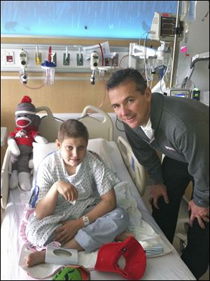 Ohio State coach Urban Meyer visited Buckeye football fan Grant Reed in December, 2012, in a Columbus hospital. Grant named his can­cer 'Mich­i­gan' and eventually beat the dis­ease.