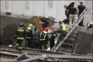 A woman is evacuated by emergency personnel at the scene of a train derailment in Santiago de Compostela, Spain.