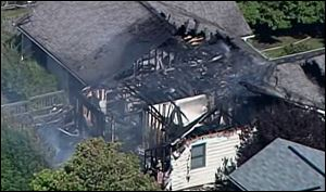 Smoke rises from a house in Columbus, Ind., after a small plane crashed into the home injuring two people who were on the plane. A woman who lives in the house and was home at the time of the crash was not injured.